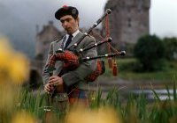 Man with bagpipes, Eilean Donan Castle, Highlands, Scotland, (...)